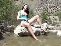 Nature loving brunette babe gets naked in a pond and masturbates